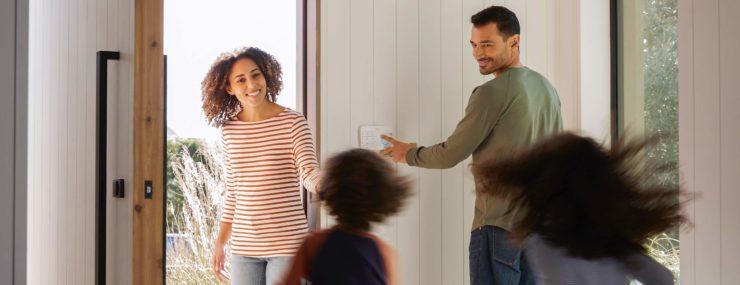 Un teclado Ring Alarm junto a la puerta principal, con el papá activándolo y la mamá viniendo a buscar a los dos niños.